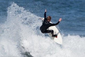 Male surfer does a top turn at Morro Rock. Scenes from a walk ne